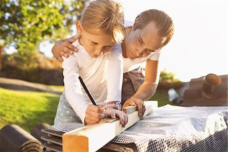 Father assisting daughter in measuring plank Stock Photo - Premium Royalty-Free, Code: 698-08008075