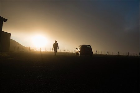 Silhouette man walking by car on field against sky during sunset Stock Photo - Premium Royalty-Free, Code: 698-08008112