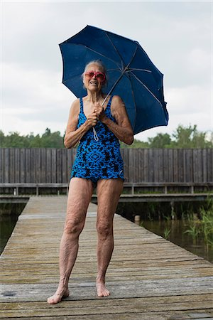 Portrait of happy senior woman in swimwear holding umbrella while standing boardwalk Stock Photo - Premium Royalty-Free, Code: 698-08008122