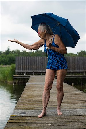 Senior woman in swimwear with umbrella gesturing while standing boardwalk at lake Stock Photo - Premium Royalty-Free, Code: 698-08008123