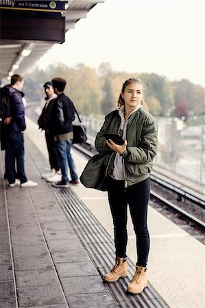 Full length of female university student holding digital tablet at subway station with friends in background Stock Photo - Premium Royalty-Free, Code: 698-08008134