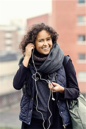 Portrait of happy female university student in warm clothing wearing headphones outdoors Stock Photo - Premium Royalty-Free, Code: 698-08008139