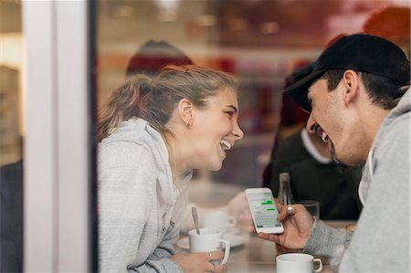european cafe bar - View of happy young couple using smart phone in cafe through glass Stock Photo - Premium Royalty-Free, Code: 698-08008166