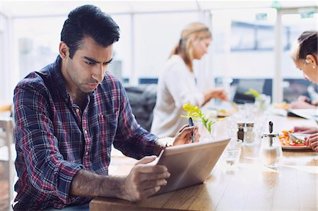 small business - Serious man using digital tablet with friends in background at cafe Stock Photo - Premium Royalty-Free, Code: 698-08008198