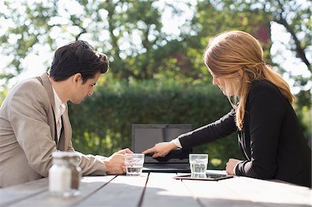 sold sign - Businesswoman discussing with male colleague through laptop at outdoor cafe Stock Photo - Premium Royalty-Free, Code: 698-08008218