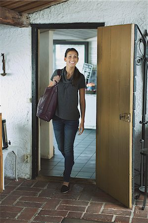 front - Full length of happy woman entering a house Stock Photo - Premium Royalty-Free, Code: 698-08008211