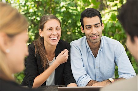 Happy business couples discussing using digital tablet at outdoor restaurant Stock Photo - Premium Royalty-Free, Code: 698-08008223