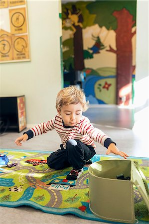 Boy removing toys from box in kindergarten Stock Photo - Premium Royalty-Free, Code: 698-08008298