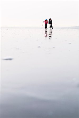 Father and daughter ice-skating on frozen lake Stock Photo - Premium Royalty-Free, Code: 698-08008303