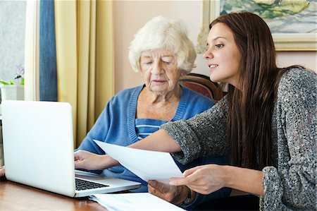 senior women - Grandmother and granddaughter with document using laptop at home Stock Photo - Premium Royalty-Free, Code: 698-08081486