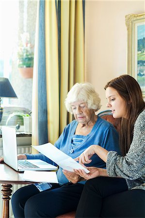 Grandmother and granddaughter reading document while using laptop at home Stock Photo - Premium Royalty-Free, Code: 698-08081487