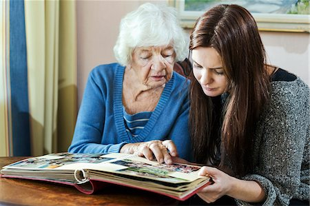 Grandmother and granddaughter looking at photo album in house Stock Photo - Premium Royalty-Free, Code: 698-08081488
