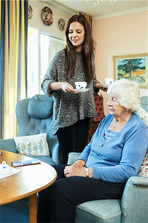 Young woman holding coffee cups while standing by grandmother at home Stock Photo - Premium Royalty-Free, Code: 698-08081489