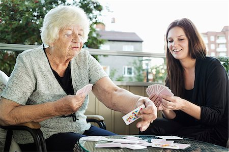 senior women - Grandmother and granddaughter playing cards on porch Stock Photo - Premium Royalty-Free, Code: 698-08081482
