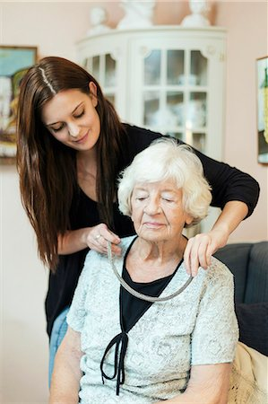 Granddaughter putting on necklace to grandmother at home Stock Photo - Premium Royalty-Free, Code: 698-08081483