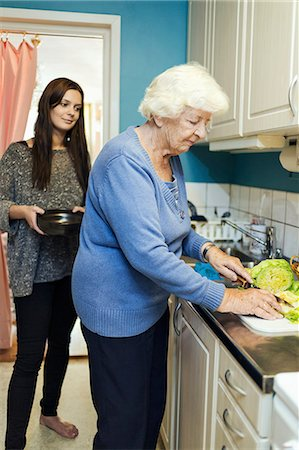 senior women - Young woman looking at grandmother preparing food in kitchen Stock Photo - Premium Royalty-Free, Code: 698-08081494