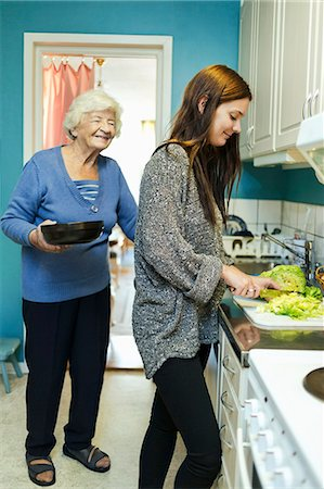 Happy elderly woman with granddaughter preparing food in kitchen at home Stock Photo - Premium Royalty-Free, Code: 698-08081496