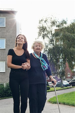 Granddaughter assisting grandmother to walk on footpath Stock Photo - Premium Royalty-Free, Code: 698-08081497
