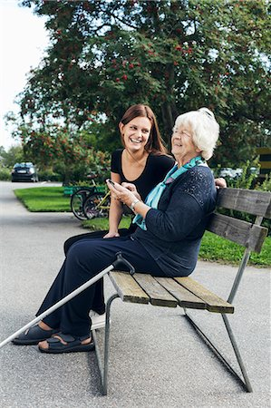 people sitting on bench - Happy grandmother and granddaughter using mobile phone on park bench Stock Photo - Premium Royalty-Free, Code: 698-08081498