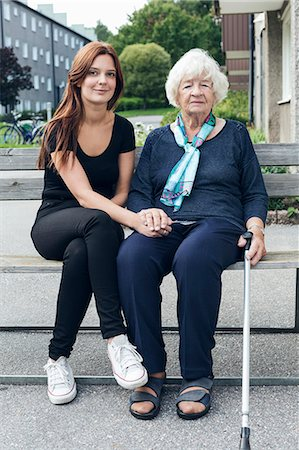 Portrait of smiling woman sitting with granddaughter on bench outdoors Stock Photo - Premium Royalty-Free, Code: 698-08081499
