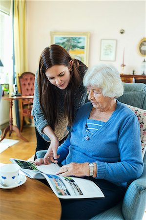 Grandmother and granddaughter reading magazine together in living room Stock Photo - Premium Royalty-Free, Code: 698-08081492