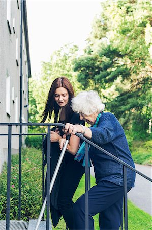 Young woman helping grandmother to climb steps outdoors Stock Photo - Premium Royalty-Free, Code: 698-08081504