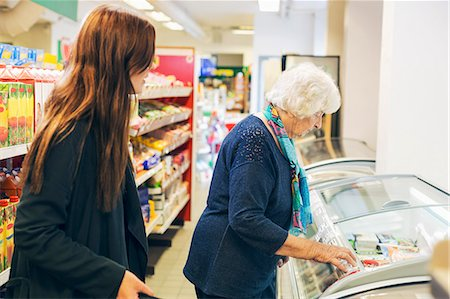 Young woman looking at grandmother shopping in supermarket Stock Photo - Premium Royalty-Free, Code: 698-08081505