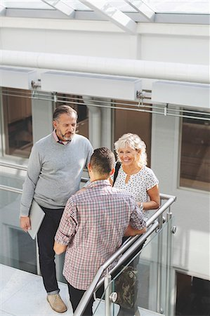 Businesspeople discussing by railing in office Stock Photo - Premium Royalty-Free, Code: 698-08081509