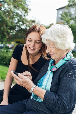 Young woman looking at grandmother using smart phone at park Stock Photo - Premium Royalty-Free, Code: 698-08081502