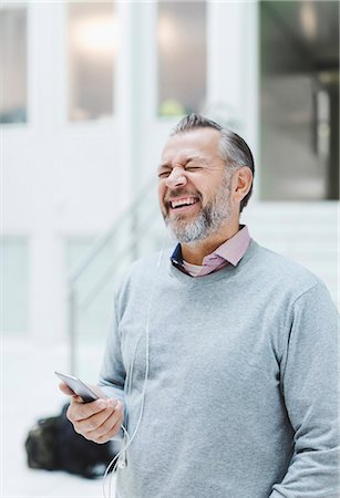 Businessman laughing while communicating through headphones in office Stock Photo - Premium Royalty-Free, Code: 698-08081517