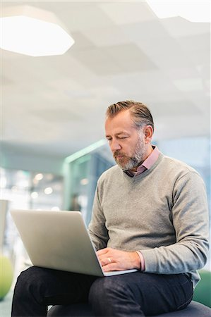 Businessman using laptop at modern office lobby Stock Photo - Premium Royalty-Free, Code: 698-08081513
