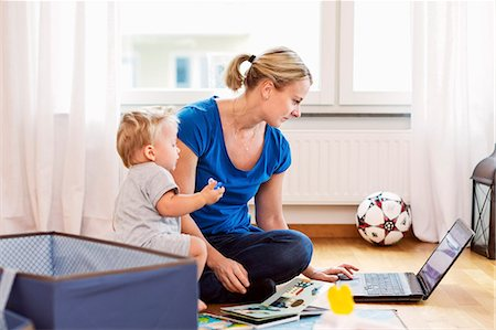 Baby boy with mother using laptop at home Stock Photo - Premium Royalty-Free, Code: 698-08081539