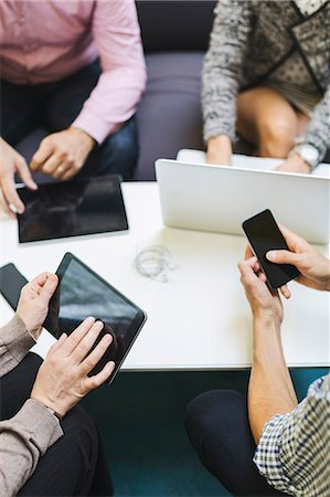 Midsection of businesspeople using technologies at table in office Stock Photo - Premium Royalty-Free, Code: 698-08081530