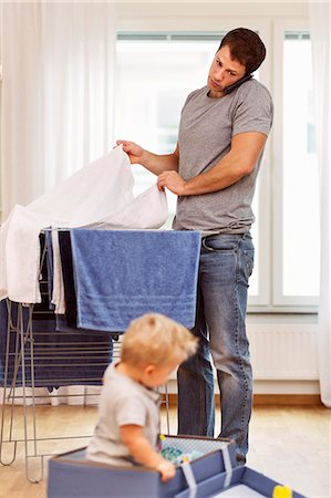 Father using mobile phone while drying clothes with baby boy playing at home Stock Photo - Premium Royalty-Free, Code: 698-08081541