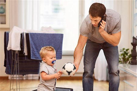 Father using mobile phone while giving ball to baby boy at home Stock Photo - Premium Royalty-Free, Code: 698-08081543