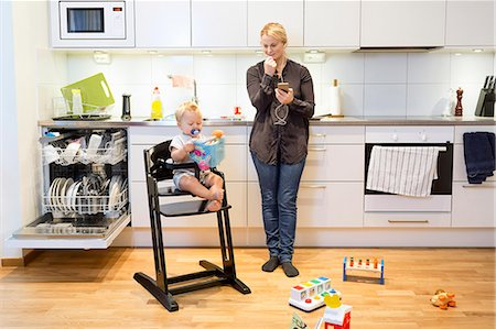 Mother talking on mobile phone in kitchen while baby boy sitting on high chair Stock Photo - Premium Royalty-Free, Code: 698-08081558