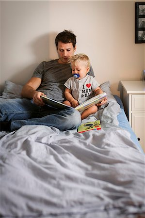 focus on background - Man reading book with baby boy in bedroom Stock Photo - Premium Royalty-Free, Code: 698-08081559