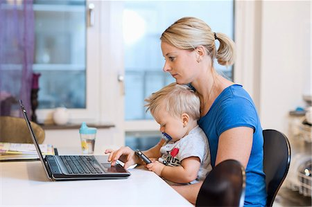 Mother working on laptop while baby boy using smart phone on her lap at home Stock Photo - Premium Royalty-Free, Code: 698-08081552
