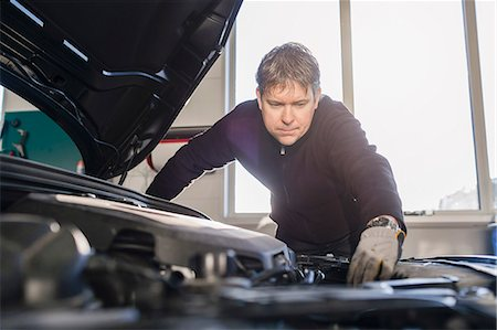focus on background - Mechanic repairing car engine in auto repair shop Stock Photo - Premium Royalty-Free, Code: 698-08081583