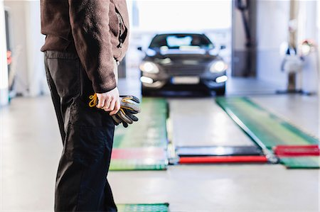 Midsection of mechanic standing in front of car coming towards hydraulic lift Stock Photo - Premium Royalty-Free, Code: 698-08081593