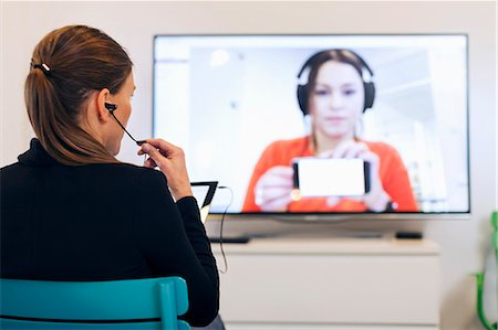 Rear view of businesswoman using in-ear headphones during conference call in creative office Stock Photo - Premium Royalty-Free, Code: 698-08081617