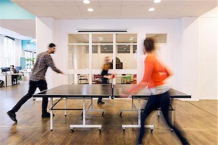 Blurred motion of business people playing table tennis in creative office Stock Photo - Premium Royalty-Free, Code: 698-08081613