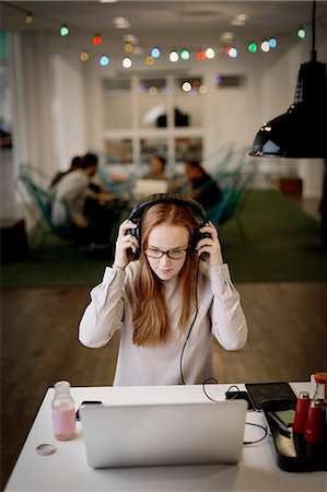 Businesswoman wearing headphones while working late on laptop in creative office Stock Photo - Premium Royalty-Free, Code: 698-08081629