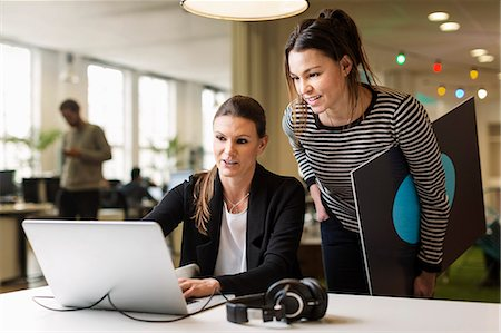Businesswomen discussing over laptop in creative office Stock Photo - Premium Royalty-Free, Code: 698-08081623