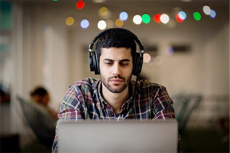 Businessman wearing headphones while working late on laptop in creative office Stock Photo - Premium Royalty-Free, Code: 698-08081631