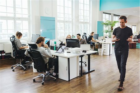 Businessman walking by colleagues working at desk in creative office Stock Photo - Premium Royalty-Free, Code: 698-08081644