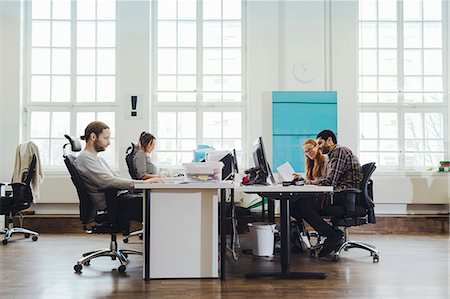 Business people working at desks in creating workspace Stock Photo - Premium Royalty-Free, Code: 698-08081647