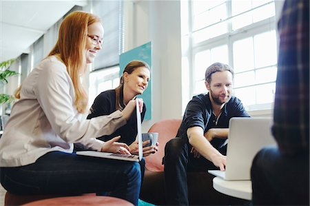 Businesspeople using laptop together in creative office Stock Photo - Premium Royalty-Free, Code: 698-08081656