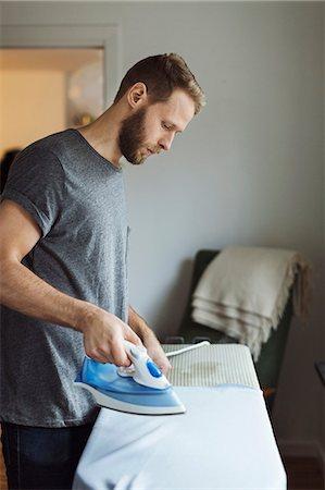 Side view of man ironing shirt Stock Photo - Premium Royalty-Free, Code: 698-08081754