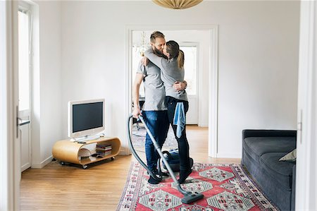 Full length of couple kissing while cleaning home Stock Photo - Premium Royalty-Free, Code: 698-08081779